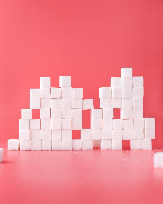 a stack of sugar cubes in front of a red pink background