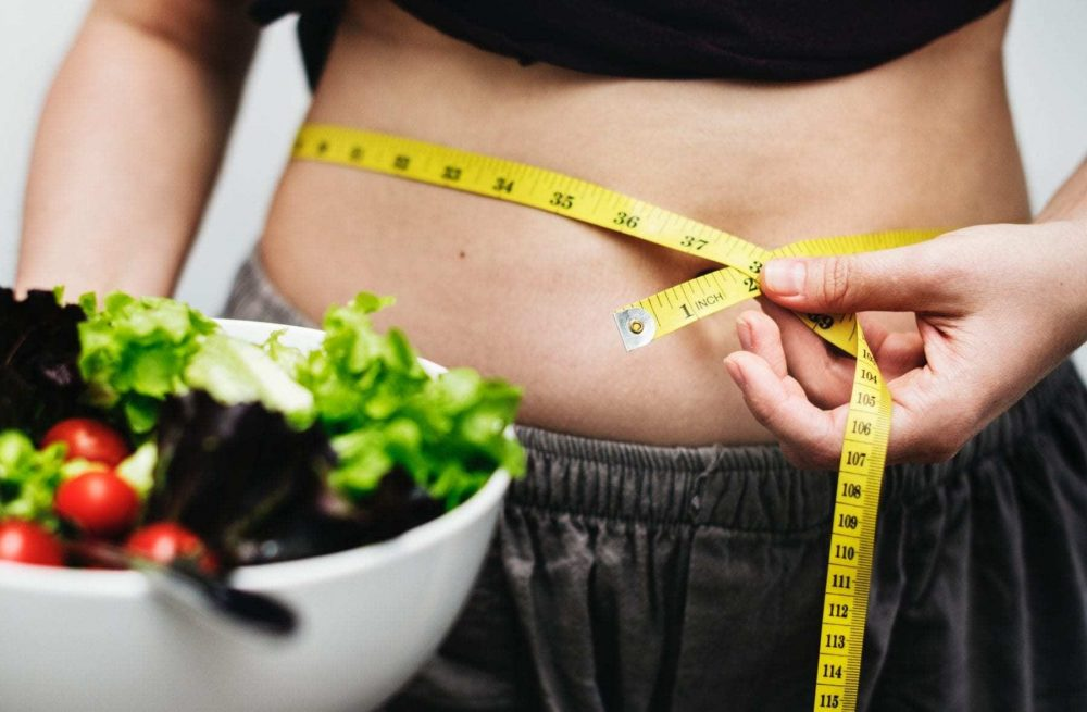 woman measuring waist and holding salad wanting to lose weight