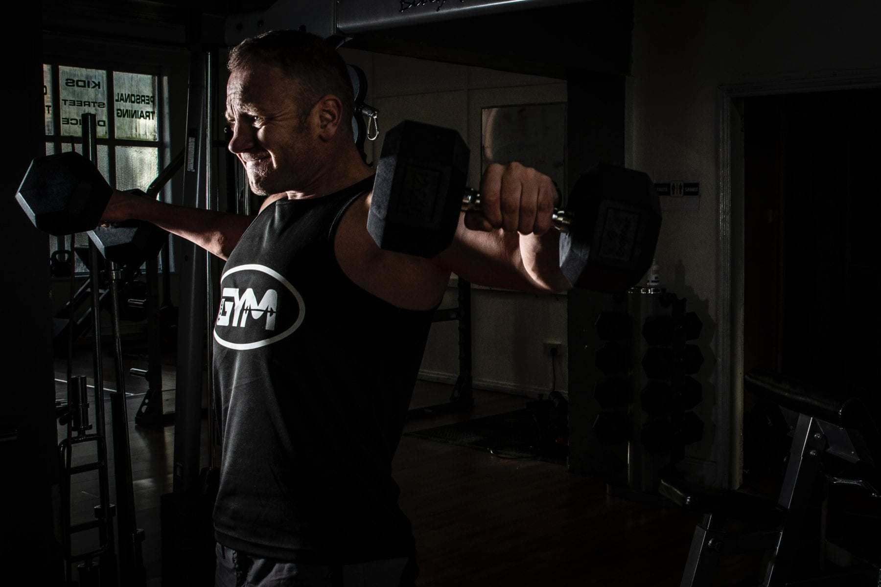 man lifting dumbells against a dark background