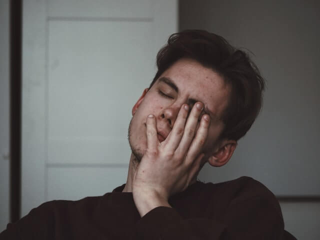 man with headache and hand on face