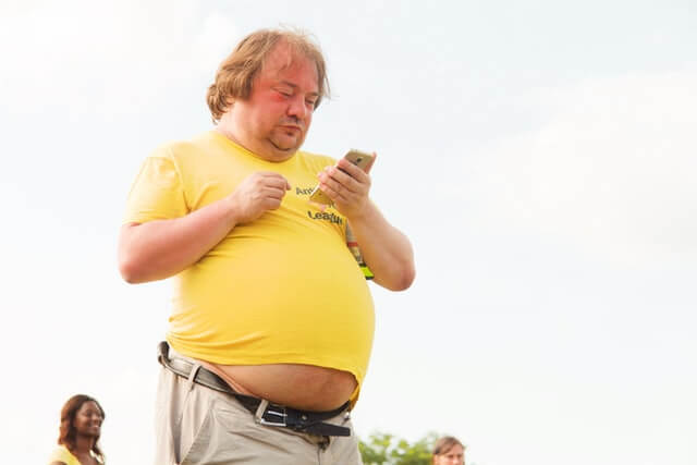 man looking on phone at how to lose belly fat fast