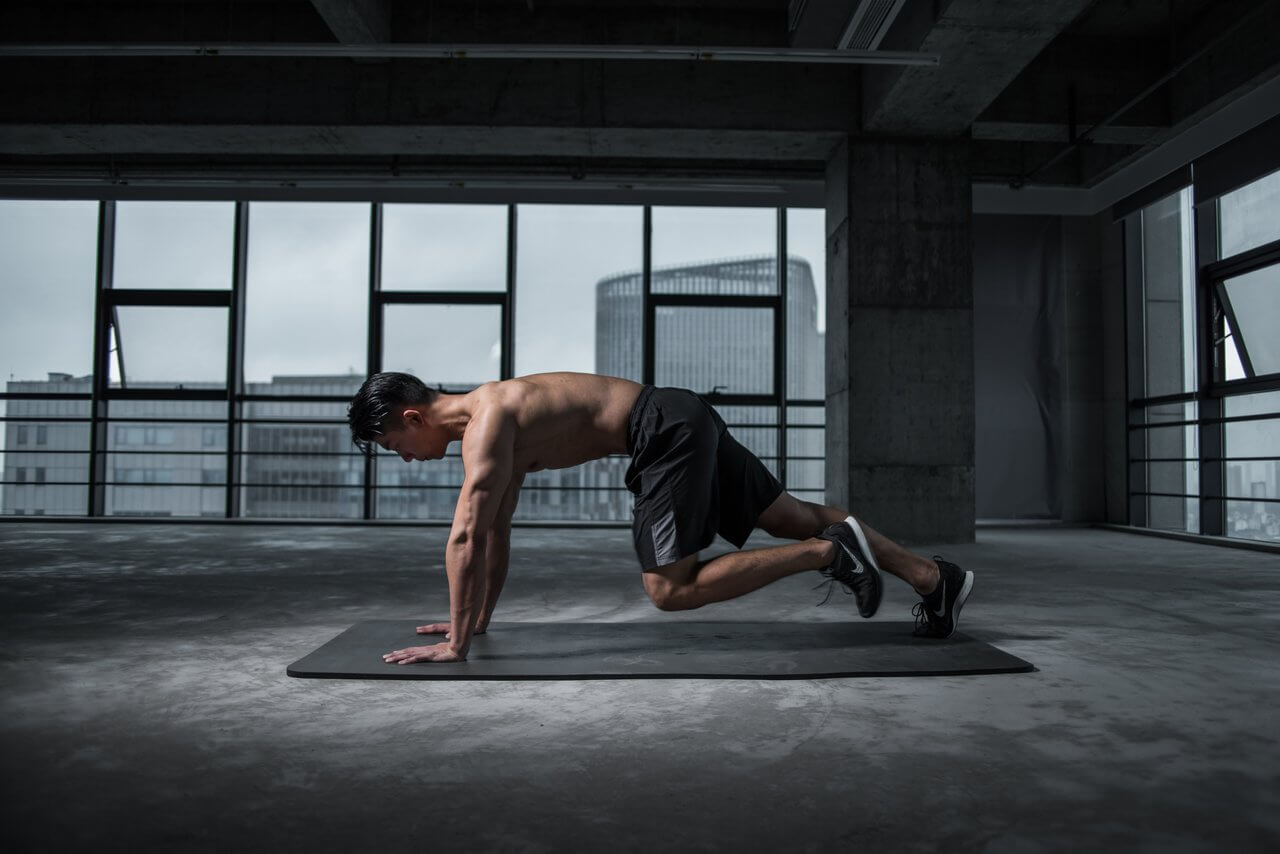 man on exercise mat, doing mountain climbers