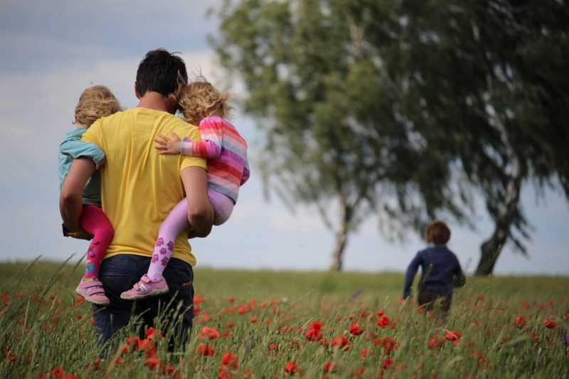 dad carrying kids in a field