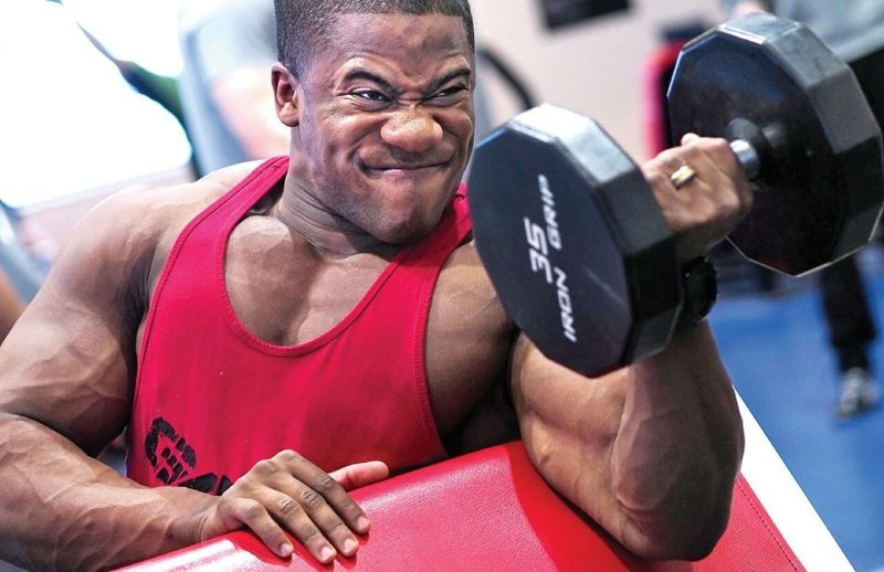 bodybuilder holding a dumbbell straining