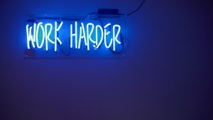 neon sign saying work harder